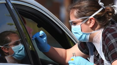 A medical worker takes a swab at a drive-in Covid-19 testing centre in Chessington.