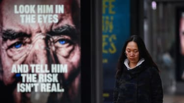 A member of the public walks past a Covid warning advert.