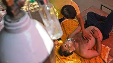 A Covid patient breathes with the help of oxygen in a tent outside a Sikh Gurdwara