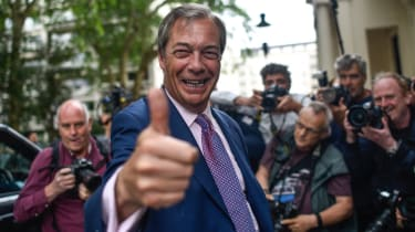 Nigel Farage gives a thumbs up to waiting photographers.
