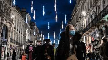 Shoppers walk under Christmas decorations in Bordeaux