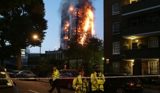 Police man a cordon as fire engulfs Grenfell Tower