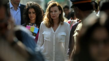 Valerie Trierweiler (C), the ex-partner of French President Francois Hollande, surrounded by security guards and officials, arrives at the Ekta Nagar slum area in Mumbai on January 28, 2014.