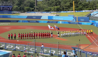 The Japan and Australia women's softball teams line up ahead of the opening match at Tokyo 2020