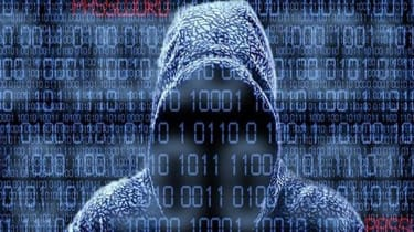Hooded man at a computer keyboard.