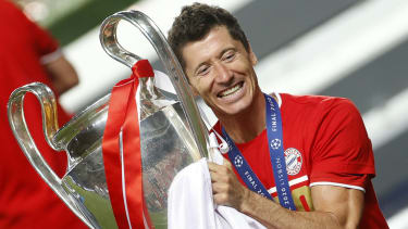 Bayern Munich striker Robert Lewandowski holds the Champions League trophy