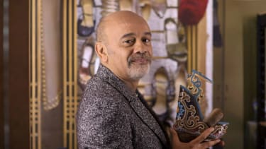 Shoe designer Christian Louboutin poses with one of his creations