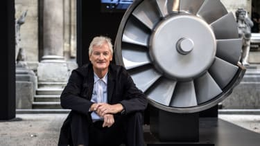 James Dyson, poses next to the model of an engine.
