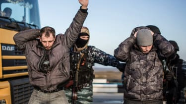 Men hold their hands up on their heads as they are searched by pro-Russian servicemen at Chongar checkpoint blocking the entrance to Crimea on March 10, 2014. Russia vowed on March 10 to unve