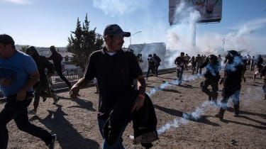 US Border and Customs fire tear gas as migrants storm the border crossing
