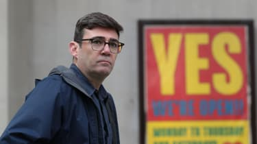 Mayor of Greater Manchester Andy Burnham stands in front of a sign advertising an open business in the city's centre.