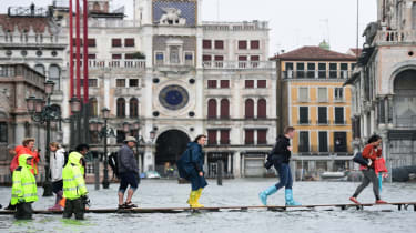 People walk on a footbridge in the flooded St. Mark's Square during a high-water (Acqua Alta) alert in Venice on October 29, 2018. - The flooding, caused by a convergence of high tides and a