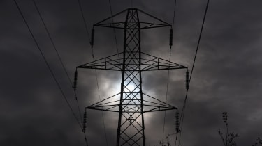 WINSCOMBE, UNITED KINGDOM - NOVEMBER 06:The sun goes behind an electricity pylon that is sited besides the M5 motorway near Winscombe on November 6, 2012 in Somerset, England. The National Gr