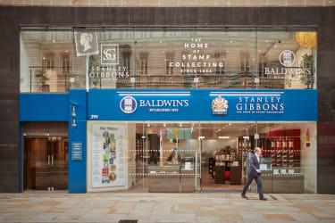 A man walking past a Stanley Gibbons shopfront