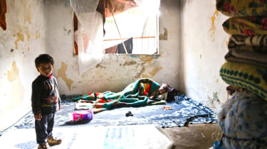 A sick Syrian woman lies as her son stands in a evacuated building on January 27, 2014 in the Kucukpazar district of Istanbul. Syrians fill houses which have been evacuated for urban developm
