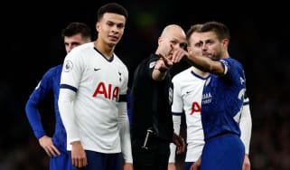 English referee Anthony Taylor (C) points out to players where comments and objects are coming from in the crowd during the English Premier League football match between Tottenham Hotspur and