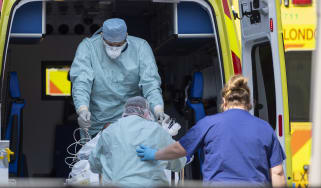 NHS workers in PPE take a patient from an ambulance at St Thomas' Hospital.