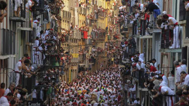 People standing on balconies look at participants as they run in front of Alcurrucen's bulls during the first bull run of the San Fermin Festival, on July 7, 2013, in Pamplona, northern Spain
