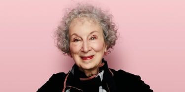 Margaret Atwood seen from the shoulders up, smiling against a pink background