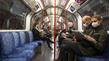 A couple sit on the Central Line Tube wearing protective face masks while reading a newspaper.