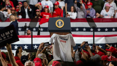 A woman holds a Trump 2024 t-shirt at a rally during the 2020 election.