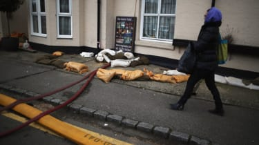 DATCHET, UNITED KINGDOM - FEBRUARY 17:A woman navigates past sandbags on February 17, 2014 in Chertsey, United Kingdom. The Environment Agency continues to issue severe flood warnings for a n