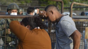 Relatives of inmates wait for news after a prison riot in Guayaquil, Ecuador