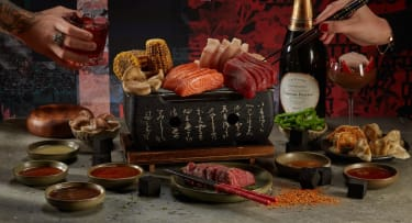 Two hands reaching from either side of the image above a spread of meat, fish, vegetables, bowls of dipping sauce and a Hibachi grill