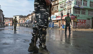 Indian security personnel stand guard on a street during a curfew in Srinagar on August 8, 2019, as widespread restrictions on movement and a telecommunications blackout remained in place aft
