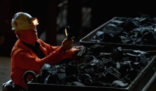 A coal miner inspects a piece of coal.