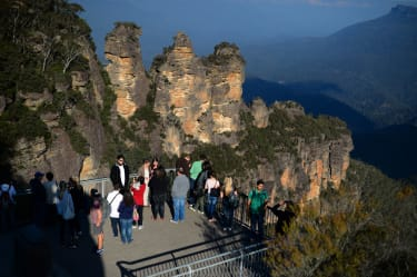 In this picture taken on May 12, 2013 people visit the 'Three Sisters' rock formation in the Blue Mountains. The Blue Mountains is a mountainous region in New South Wales, some 50 kilometers