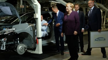 ZWICKAU, GERMANY - NOVEMBER 04: German Chancellor Angela Merkel (C) visits the assembly line of the new Volkswagen ID.3 electric car accompanied by Herbert Diess (L of Merkel), head of Volksw