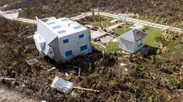 A house lies on its side among destruction
