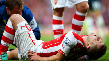 Jack Wilshere of Arsenal receives treatment during the Barclays Premier League match between Arsenal and Tottenham Hotspur