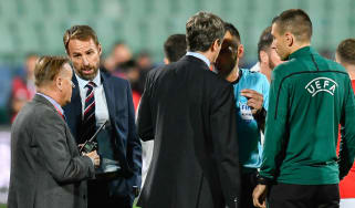 England head coach Gareth Southgate speaks with match officials during a break in play