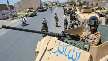 An Afghan National Army commando stands guard on top of a vehicle along a road in Herat province on 1 August 2021