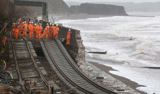DAWLISH, UNITED KINGDOM - FEBRUARY 05:Railway workers inspect the main Exeter to Plymouth railway line that has been closed due to parts of it being washed away by the sea at Dawlish on Febru