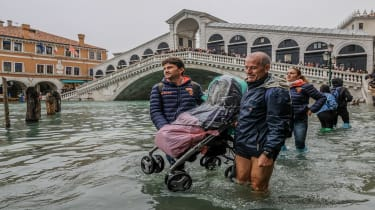 """VENICE, ITALY - OCTOBER 29: Tourists carry a stroller through the flood waters on October 29, 2018 in Venice, Italy. Today due to the exceptional level of the """"acqua alta"""" that reaced 156 cm"""