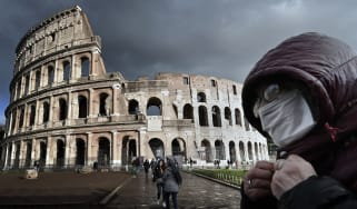 A masked visitor to the Colosseum in Rome