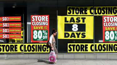 A pedestrian walks past a shop with a closing down sale promotion in Liverpool