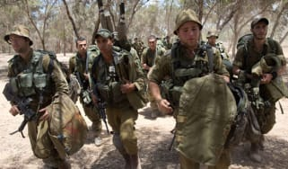 Israeli soldiers walk to their deployment area on the border with Gaza