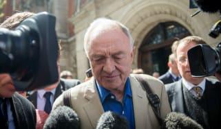 Ken Livingstone is flanked by journalists in London