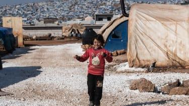 IDLIB, SYRIA - FEBRUARY 20: A displaced Syrian girl runs in a refugee camp in Atmeh village near the Syrian-Turkish border on February 20, 2020 in Idlib, Syria. Turkey's President Recep Tayyi