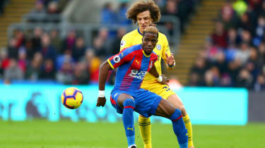 Crystal Palace forward Wilfried Zaha is challenged by Chelsea defender David Luiz