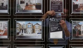 An estate agent hangs a promotional sign in the shop window