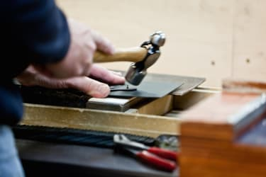 An artisan hammers the leather corners of a Globe-Trotter classic suitcase