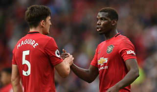 Manchester United centre-half Harry Maguire shakes hands with team-mate Paul Pogba