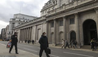 A pedestrian wearing a protective face mask walks past the the Bank of England in the City of London