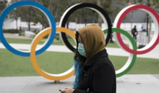 A woman wearing a face mask walks past the Olympic rings in Tokyo