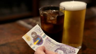 A customer pays for drinks at a pub using cash